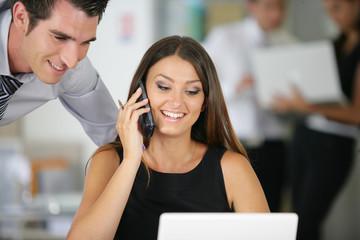 femme souriante avec téléphone sans fil au bureau