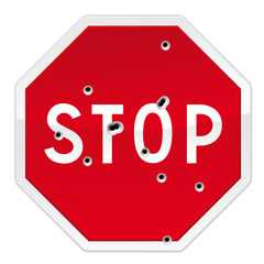 Stop road sign with bullets impacts