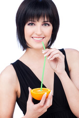Pretty woman drinking juice from slice of orange, isolated