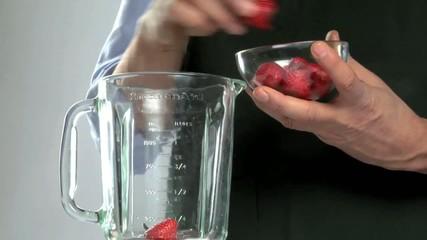 Uomo prepara frullato di fragole