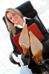 young business woman sitting on desk