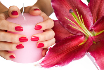 Hands with pink manicure, candle and lily