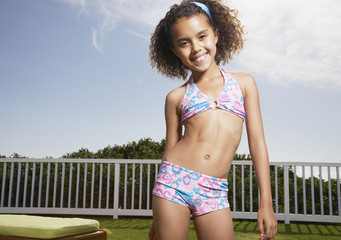 Girl standing outdoors in swimsuit smiling