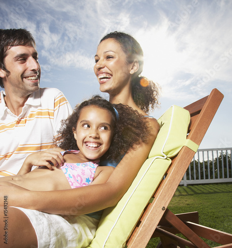 Woman and man with girl snuggling outdoors in summer