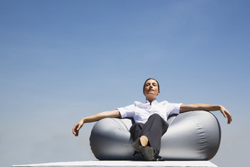 Businesswoman sitting on beanbag chair outdoors with eyes closed