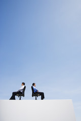 Two businessmen on wall with office chairs back to back