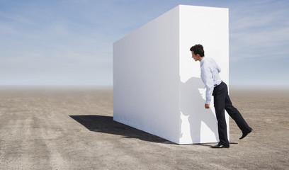 Businessman peering around wall outdoors