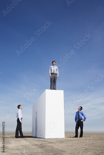 Businessman standing on wall outdoors with two men watching