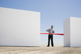 Businessman cutting red tape or ribbon between two walls