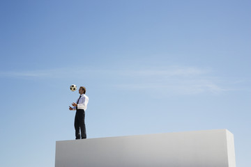 Businessman standing on wall with soccer ball outdoors