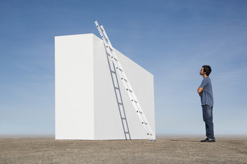 Man looking at ladder against wall outdoors