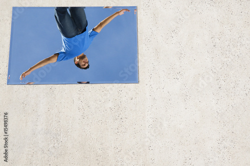 Man with arms up reflected in mirror on ground