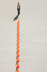 Woman looking at row of traffic cones