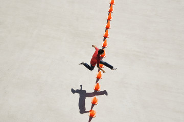 Man leaping over row of traffic cones