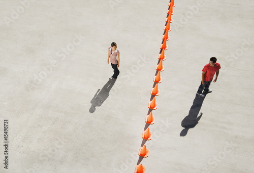 Man and woman on either side of row of traffic cones looking back