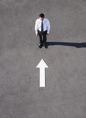 Arrow on pavement pointing toward businessman