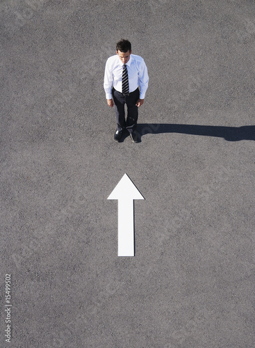 Arrow on pavement pointing toward businessman