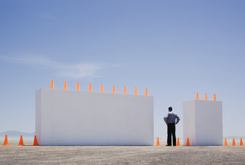 Man standing between two monolithic barriers lined with safety cones
