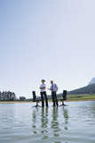 Businesswoman and man standing on water with office chairs
