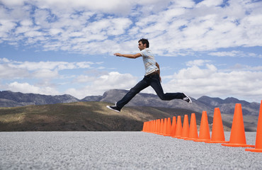 Man jumping over safety cones