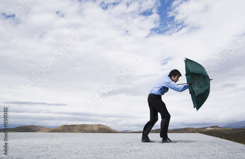 Man using umbrella to protect himself from the wind