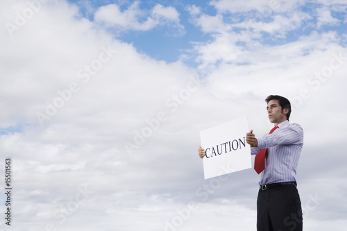 Man holding a caution placard