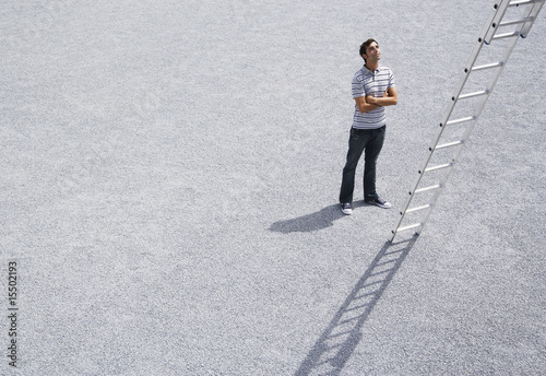 Man looking up at ladder outdoors with arms crossed