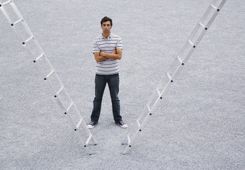 Man standing with arms crossed outdoors with two ladders
