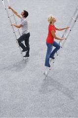 Man and woman climbing ladder outdoors