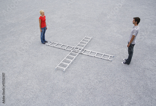 Man and woman standing outdoors with two ladders
