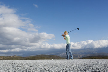 Woman playing golf on pebbled terrain