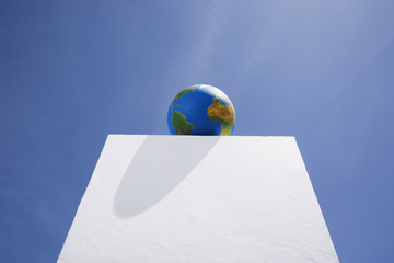 Globe atop pillar outdoors with blue sky
