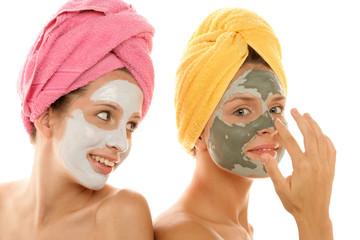 Two teenage girls applying facial cream