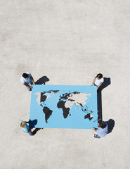 Four people holding world map outdoors