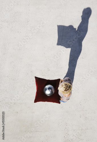 Aerial view of woman holding globe on cushion