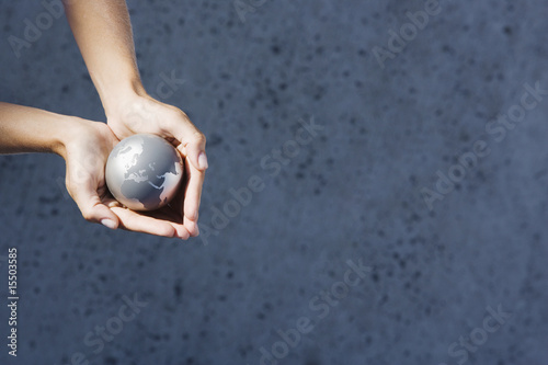 Detailed View of hands holding globe outdoors