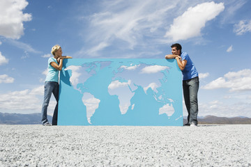 Man and woman leaning on world map outdoors