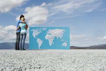 Man and woman looking at world map outdoors