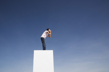 Man standing on wall outdoors shouting