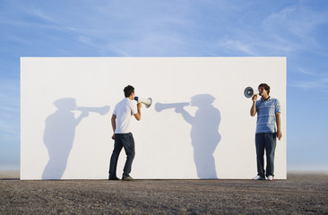 Men standing in front of wall outdoors with megaphones and shadows
