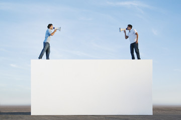 Men standing on wall outdoors with megaphones