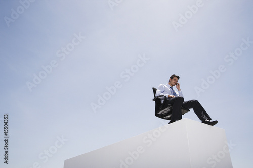Businessman with cell phone in office chair on wall outdoors