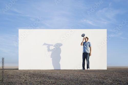 Man standing in front of wall outdoors with megaphone and shadow