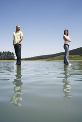 Man and woman standing on water with arms crossed back to back