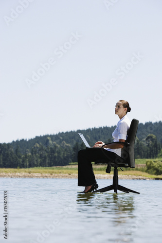 Businesswoman in office chairs on water with laptop