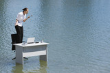 Businesswoman standing on a chair on water shouting into a telephone