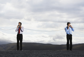 Businessmen with telephone receivers joined outdoors