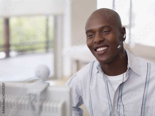 Man wearing an earpiece on his computer