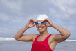 woman at the beach putting on swimming goggles
