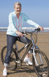 senior woman on a bike at the beach